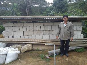 Man in Chinacla community using water for the production of construction blocks